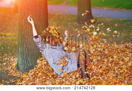 Pretty girl throws leaves in autumn park.
