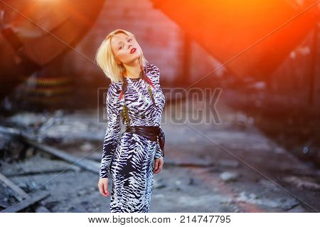 Portrait of young cute girl blonde in elegant dress posing in an abandoned building, close up. Contrast - luxurious woman on blurred background of the destroyed interior of the factory.