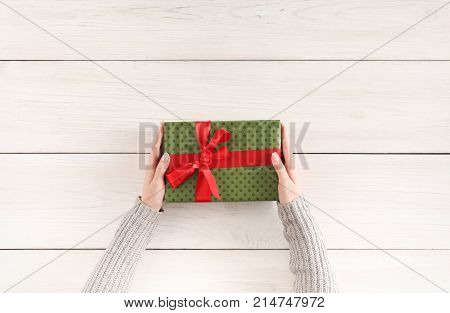Gift wrapping background. Female hands holding handmade present box in green paper against white wooden table background. Bithday or christmas preparation concept, top view, copy space