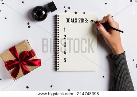 Goals plans dreams make to do list for new year 2018 christmas concept writing in notebook. Woman hand holding ink pen on notebook with gift red bow on white background. New year winter holiday xmas