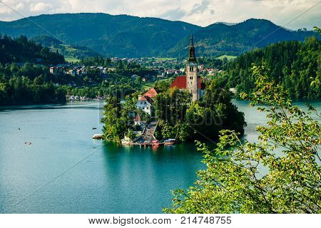 Colorful summer scene on the Bled lake with the famous Pilgrimage Church of the Assumption of Maria and Bled Castle and Julian Alps at background