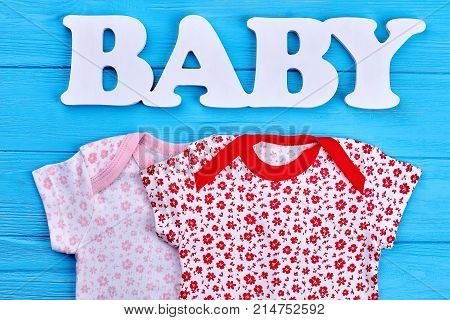 Set of patterned baby-girl clothing. New cotton apparel for newborn baby, blue wooden background. Shop natural baby clothes.