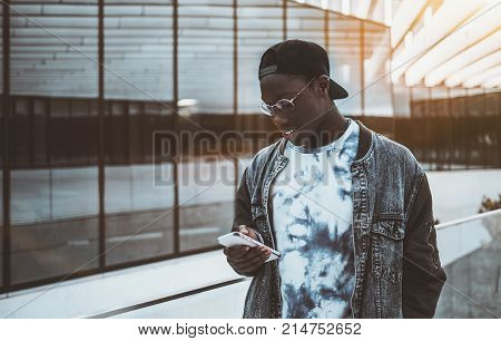 Young black student guy in jean jacket and glasses is standing outdoors in modern campus and reading SMS message from his group mate via smartphone; copy space place for advertising your logo or text