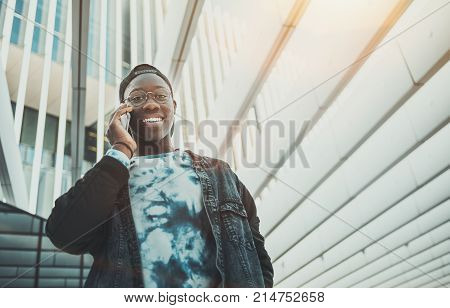 View from bottom of cheerful young African student having phone conversation outdoor with modern striped ceiling above him; smiling black undergraduate male in glasses is talking via smartphone