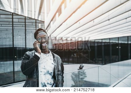 Smiling young African student in glasses and jean jacket is having phone conversation while standing outdoors in modern urban settings with copy space zone for your logo advertising or text message