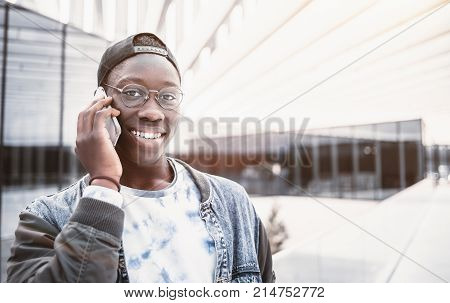 Close-up portrait of handsome cheerful African male student talking on the smartphone outdoors; young black guy having phone conversation on street; with copy space place for logo your text or advert