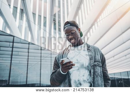 Smiling African American student in glasses cap and jean jacket is standing outdoors and typing message on his smartphone for chat with group mates; with striped futuristic building exterior behind