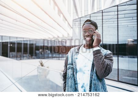 Portrait of young smiling Afro male student in jean jacket standing outdoor near glass exterior and talking on the phone with his girlfriend; with copy space zone for text your logo or advertising