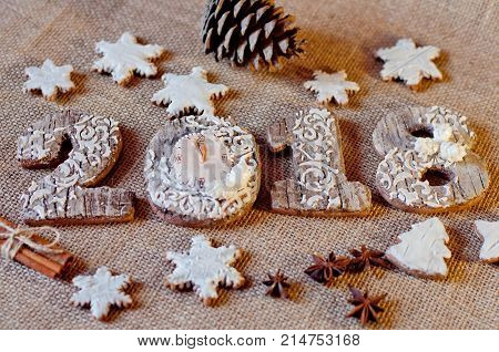 New year sweets. Honey cookies stylized as wooden numbers 2 0 1 8 and white stars laying near pine cones aniseed cinnamon sticks on brown sackcloth