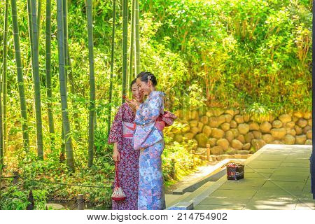 Kamakura, Japan - April 23, 2017: Japanese women wearing traditional kimono look at smartphone at forest of bamboo in Hase-dera Temple or Hase-kannon in Kamakura. Meditative and buddhism concept.