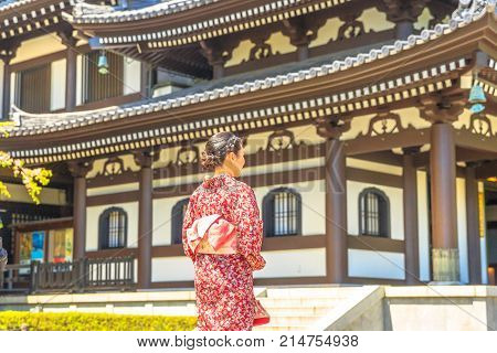 Kamakura, Japan - April 23, 2017: woman wearing japanese kimono in front of Kannon-do or Main hall of Hase-dera Temple in Kamakura. Japanese culture and lifestyle. Spring season.