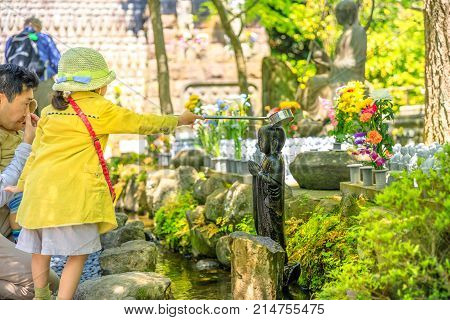 Kamakura, Japan - April 23, 2017: child worshiping of Jizo Statue pouring water on Jizo's head with a ladle. Hase-dera Temple in Kamakura. Built to house a big wooden statue of Kannon goddess of mercy