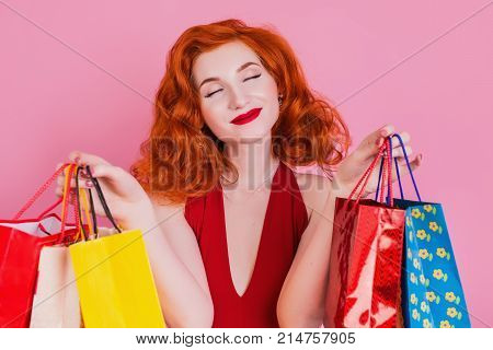 Girl in red dress with shopping bags on blue background. Black Friday shopping. A girl loves shopping. Shopping concept on a blue background. Stylish model with shopping bags. Do shopping on a black Frida