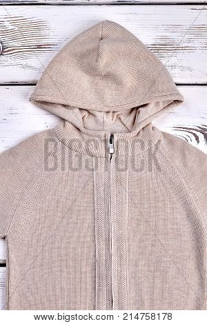 Top view of knitted sweater for children. Warm beige autumn or winter jacket with zipper. Kids clothing for casual wear.