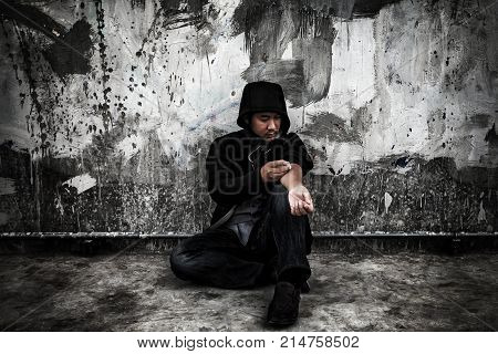 Drug abuse concept. Overdose asian male drug addict in action with drugs narcotic syringe in hand.