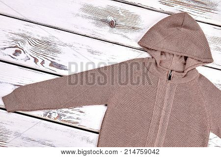 Boys hooded brown zipper cardigan. Brown color hooded knit cardigan on old wooden background.