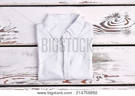 Woman white office cotton shirt. New folded white blouse for girls on old wooden background. Woman elegant cotton shirt on sale.