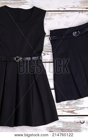 Black belted dress and skirt. School girl classic pleated black dress and skirt on old wooden background, top view.