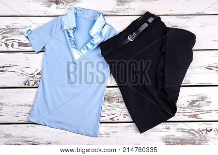 Beautiful school uniform for girls. Light blue cotton blouse and black pleated knee-length skirt, top view. New collection of school apparel for girls. poster