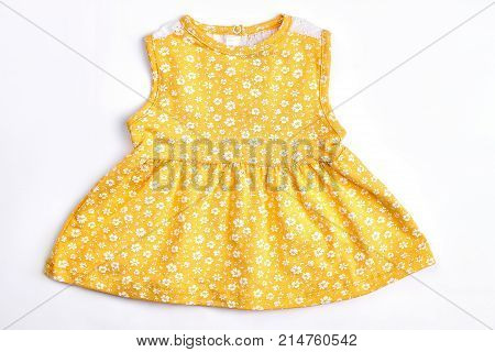 Baby-girl yellow patterned top. Newborn baby girl cotton sleeveless dress with a pattern of small white flowers, white background. Infant girl summer clothes.
