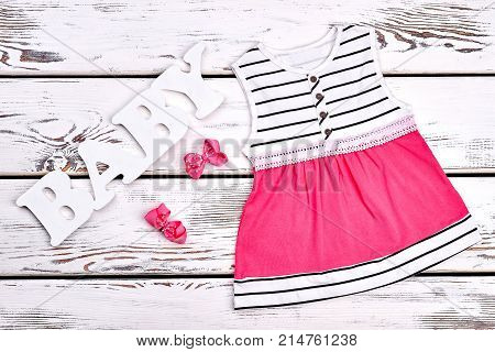 Baby-girl beautiful dress and hair bows. Infant girl cute striped and pink dres, pink hair butterfly clips on white wooden background.