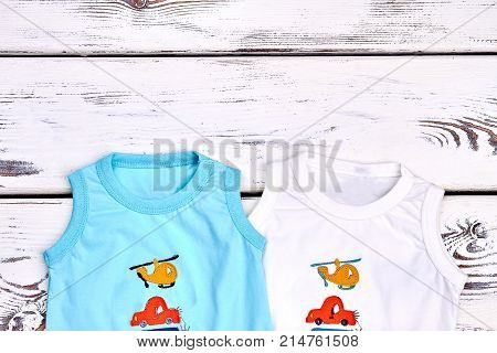 Baby boy new cartoon t-shirts. Toddler boy collection of round neck sleeveless t-shirts on white wooden background, top view. Infant boy summer clothes and copy space.