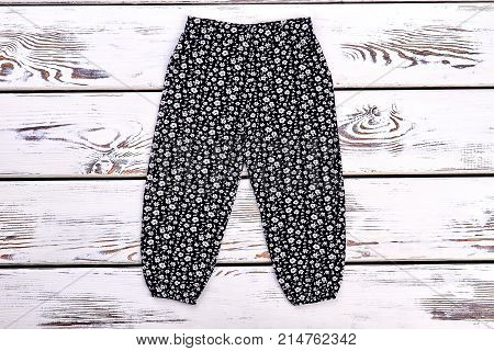 Little girl vintage print trousers. Infant girl new patterned trousers on white wooden backgroud. Kids harems on sale.