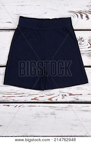 Toddler boy summer casual shorts. Childs black color short pants on white wooden background. Solid color kids shorts.