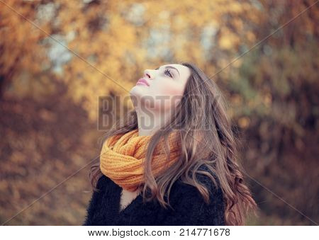 Portrait Of An Young Attractive Woman With Long Brown Hair And Bright Scarf Enjoying Her Time In The