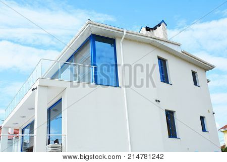 Close up on Modern House with Blinds Sun Protection with Glass Balcony. Windows in New Modern Passive House Attic with Shutters Closed and Opened Outdoors.