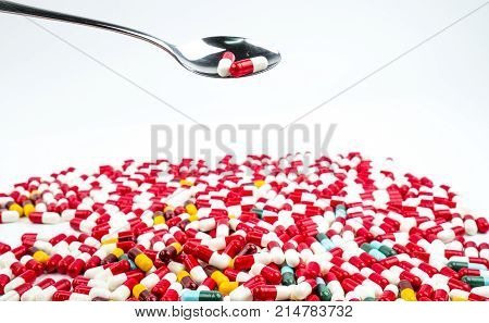 Antibiotic capsules pills in stainless steel spoon on white background with copy space. Drug resistance concept. Antibiotics drug use with reasonable and global healthcare concept.