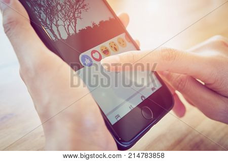 Bangkok Thailand - November 22, 2017 : hand is pressing the Facebook screen on apple iphone6 Social media are using for information sharing and networking.