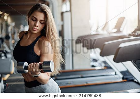Portrait of young body fitness cross athlete woman using dumbells to warm up her biceps and triceps. Looking happy and satisfied.