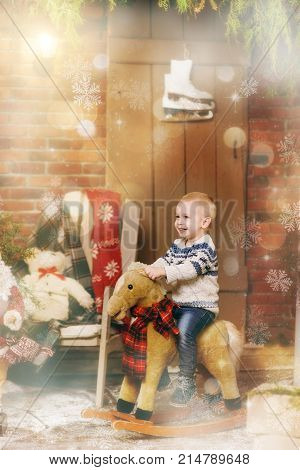 Playful Smiling Happy Little Child Boy Sitting On Rocking Horse In Decorated New Year Room At Home.