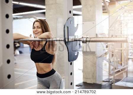 Portrait of happy body fitness woman athlete leaning on crossbar or bar-bell looking at camera laughing happy with her fit body and overall stamina and health. Being sporty is cool.