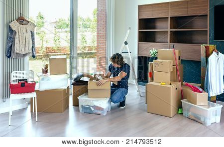 Young man unpacking moving boxes in living room