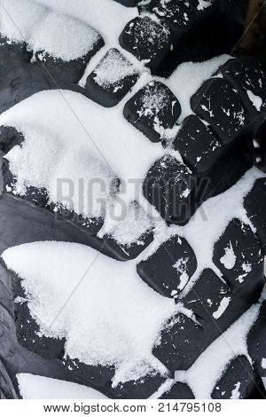 Close-up snow-covered black big automobile tire with deep tread.