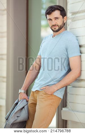 Young urban businessman professional wearing standing against business building on street and looking to camera