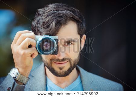 Male photographer taking picture. Portrait of handsome man with camera outdoors