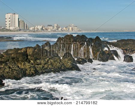 FROM BLOUBERG STRAND, CAPE TOWN, SOUTH AFRICA, ON A CLEAR DAY, WITH A ROUGH SEA WASHING OVER SOME BOULDERS IN THE FORE GROUND AND HIGH RISE BUILDINGS IN THE BACK GROUND