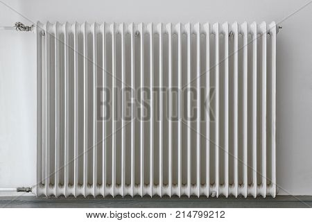 White heater radiator on a wall. Home appliance equipment.