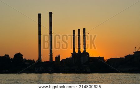 Silhouettes of the industrial chimneys at dusk