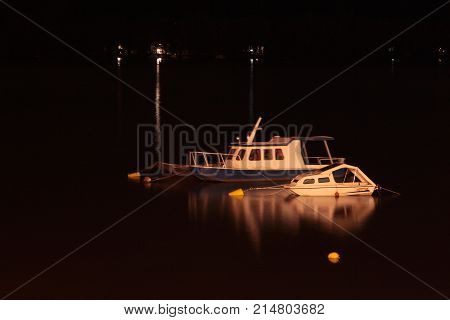 Night shot of two white small boats in a marina