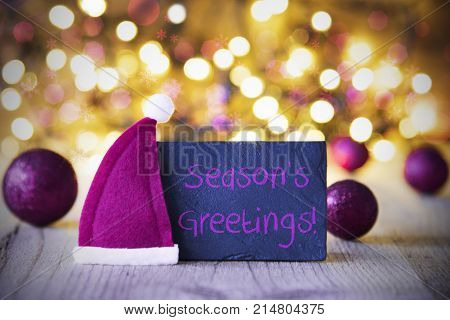 Plate With English Text Seasons Greetings. Purple Christmas Ball Ornaments And Santa Claus Hat. Wooden Background With Lights