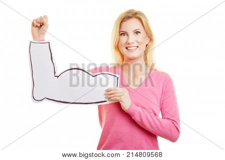 Young blonde woman holds cardboard muscles in front of her arm as a sign of strength and fitness