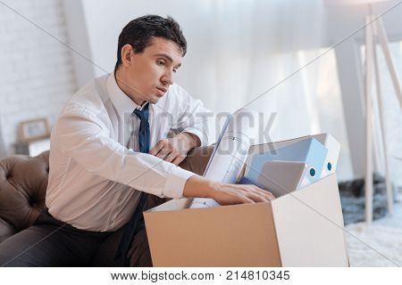 Personal things. Attentive calm jobless man sitting at home and looking at his personal things in a big box while thinking about losing his job