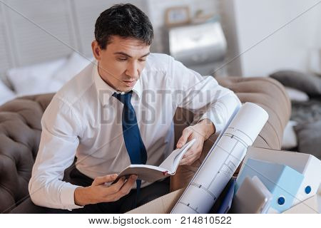 Important notebook. Calm concentrated young man looking at the notes in his notebook while sitting in front of a box with personal things and reading important information