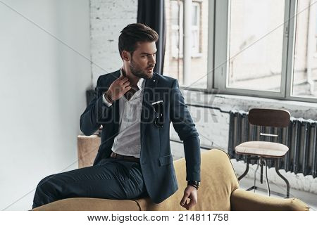 True elegance. Handsome young man in full suit adjusting his shirt and looking away while sitting on the sofa