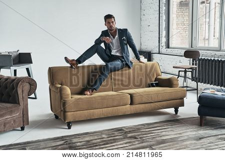 Young and successful. Good looking young man in full suit looking away while sitting on the sofa