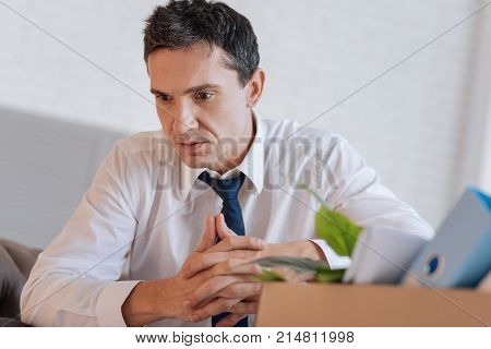 Frustration. Calm thoughtful redundant manager sitting with his fingers crossed and looking into the distance while realizing current situation